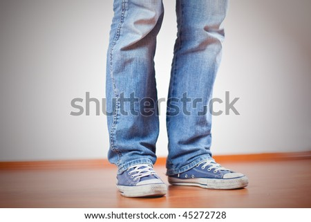 human foot with jeans and sneakers on wooden floor
