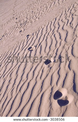 Human footprints in rippled sand, shadowed by sinking sun, diminish with distance - tilted view - stock photo