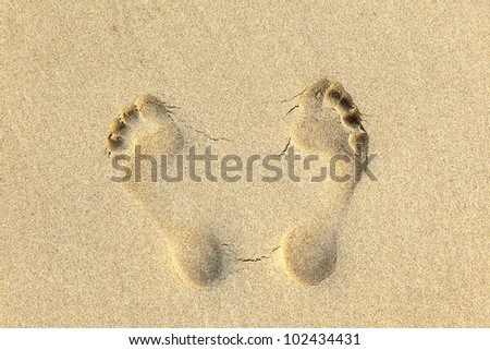 human footprints in the fine sand at the beach - stock photo