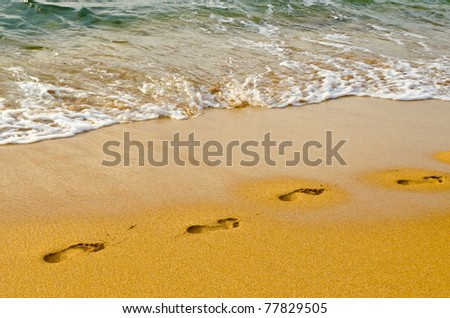Human footprints leading away from the viewer into the sea - stock photo
