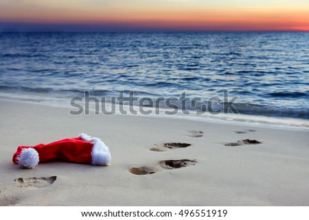 Human footprints on a sandy beach with Santa Claus hat at sunset. Deserted sea beach on Christmas evening at sunset on the horizon. Lonely Santa Claus hat on sea beach.