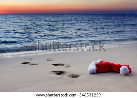 Human footprints on a sandy beach with Santa Claus hat at sunset. Throw away the cap Santa Claus with traces to the sea. Abandoned Santa hats on the evening beach. Christmas at sea.