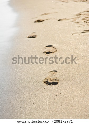 Human footprints on the beach sand. Traces on the beach of a man or a woman. Footsteps on the beach by the sea in summer - stock photo
