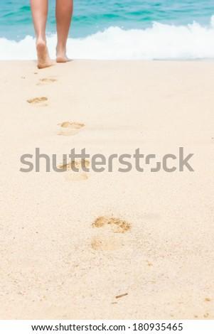 Human footprints on the white sandy beach - stock photo