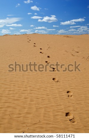 Human footprints on the yellow sand against the blue sky with clouds. Over horizont. - stock photo