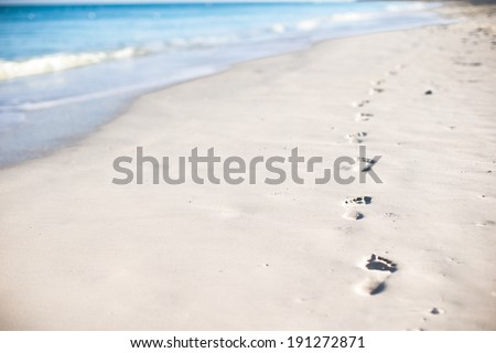 Human footprints on white sand of the Caribbean island - stock photo