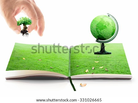 Human hand add growing tree into opening book in meadow with a earth globe of grass in a stand shows on white background. Natural energy Ecology World Environment Day Go Green CSR Eco Friendly concept - stock photo