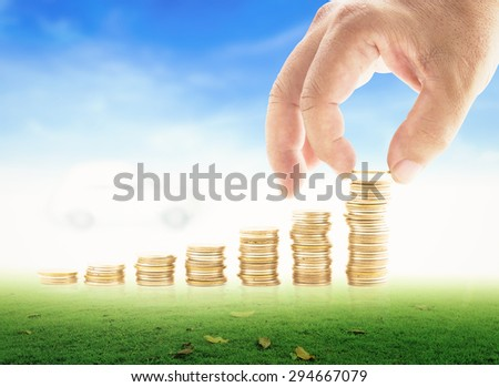 Human hand adding golden coin in the final row of golden coins over blurred white car on beautiful blue sky background. Concept for money coin, insurance, buying, renting, repair, fuel, debt, service. - stock photo