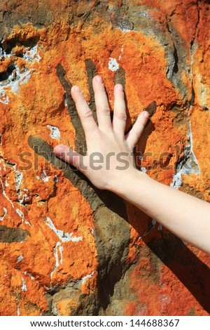 human hand and painting on rock