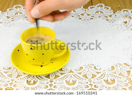 human hand  and  silver spoon stirs coffee - stock photo
