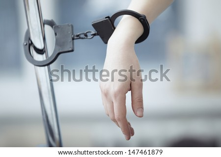Human hand bounded to the metal pole by handcuffs - stock photo