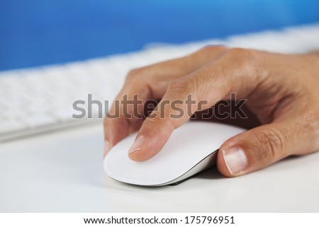 Human hand clicking on a computer mouse / Computer mouse in hand
