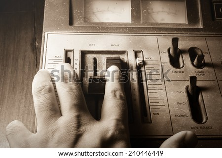 Human hand controlling radio sound,sepia filtered.  - stock photo