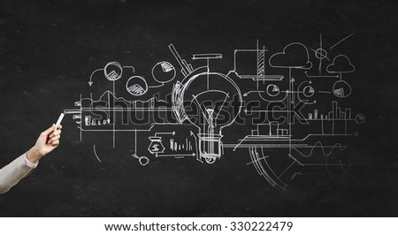 Human hand darwing light bulb as idea concept with chalk - stock photo