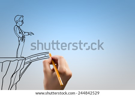 Human hand drawing caricature of man and bridge above gap - stock photo