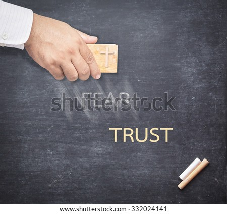Human hand erased the word FEAR from a chalkboard for changing to TRUST. Change concept. - stock photo