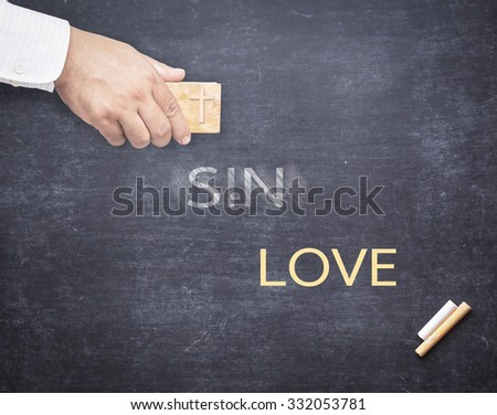 Human hand erased the word SIN from a chalkboard for changing to LOVE. Change concept. The word SIN erased from a chalkboard. Concept of Jesus erasing sin. - stock photo