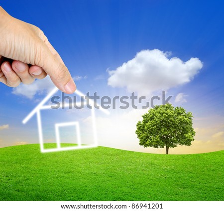 Human hand fill home on the beautiful land - stock photo