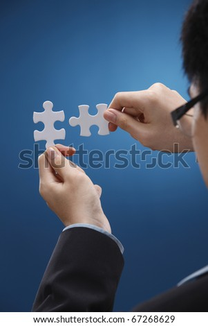 Human hand fitting two puzzle pieces together.