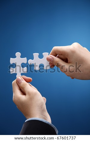 Human hand fitting two puzzle pieces together. - stock photo
