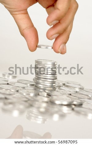 Human hand hold a coin on pile of coins - stock photo
