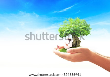 Human hand holding a beautiful asian girl reading a book under big tree on green meadow over blue sky background. World Mental Health Day concept. International Day of the Girl Childconcept. - stock photo