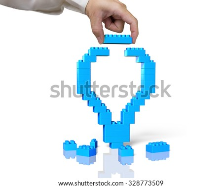 Human hand holding a blue lego block to complete light bulb shape, isolated on white background. - stock photo