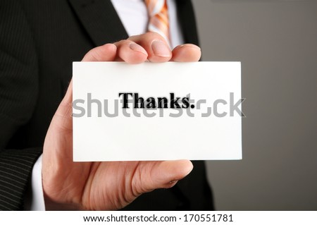 human hand holding a business card with a message thanks