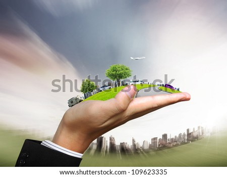 human hand holding a city and nature - stock photo