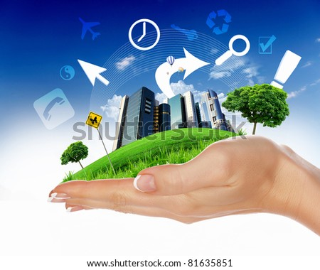 human hand holding a city on green grass hill - stock photo