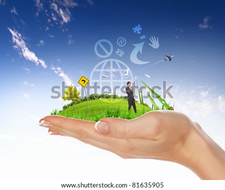 human hand holding a city on green grass hill