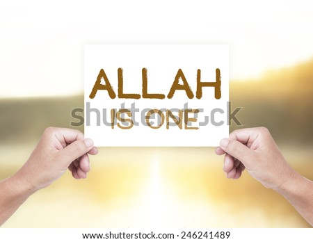 Human hand holding a handwritten text for ALLAH IS ONE over blurred nature background. - stock photo