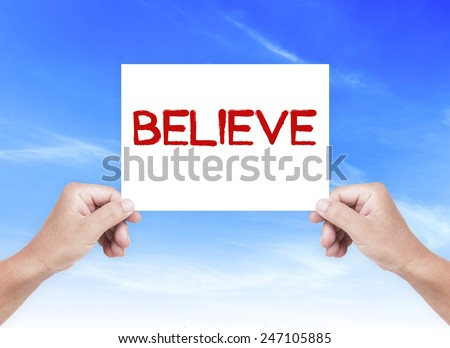 Human hand holding a handwritten text for BELIEVE over blue sky background. - stock photo