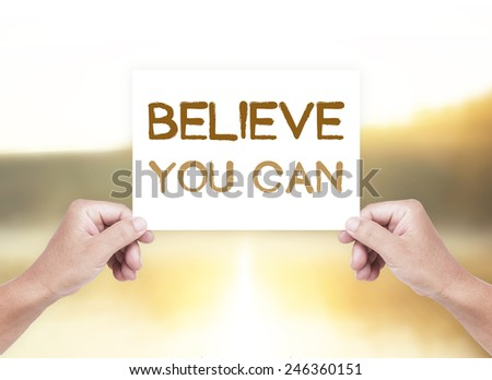Human hand holding a handwritten text for Believe You Can over blurred nature background. - stock photo