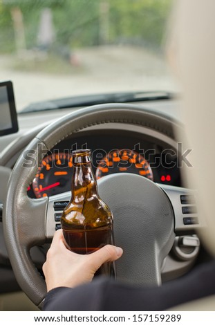 Human hand holding a liquor bottle while driving in a close up shot - stock photo