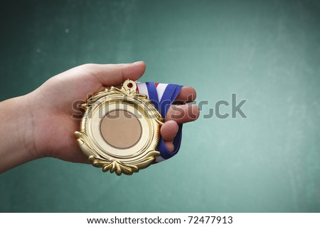 Human hand holding a medal.