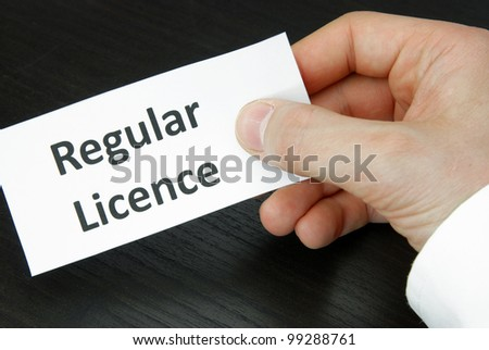 Human Hand holding a Regular Licence Sign - stock photo