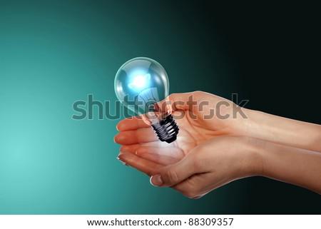 Human hand holding a shining electric bulb - stock photo