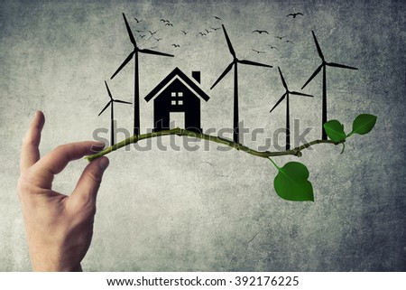 Human hand holding a tree branch. Environmental green energy concept. Silhouette of house, wind turbine and birds flying - stock photo