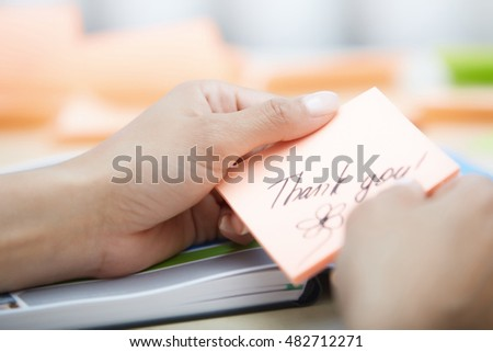 Human hand holding adhesive note with Thank you text
