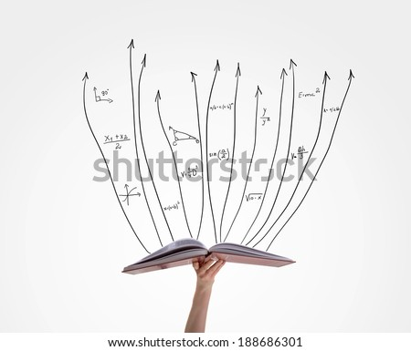 Human hand holding book with flying math formulas - stock photo