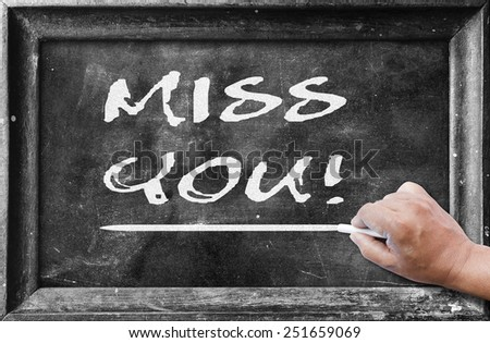 Human hand holding chalk and writing text for MISS YOU! on blackboard. - stock photo