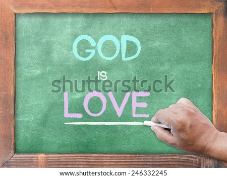 "Human hand holding chalk and writing text form bible ""GOD is LOVE"" on green board. - stock photo"