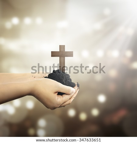 Human hand holding christian cross with soil on the hand over blur background - stock photo