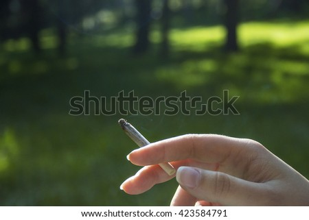 Human hand holding cigarette over green forest background