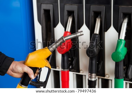 Human hand holding gasoline station gas fuel pump - stock photo