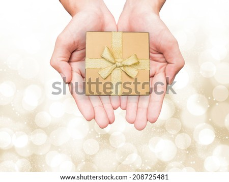 Human hand holding golden gift box  for X'mas on gold bokeh background - stock photo