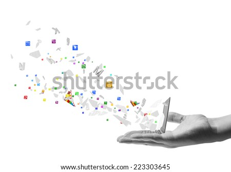 Human hand holding laptop with icons flying out - stock photo