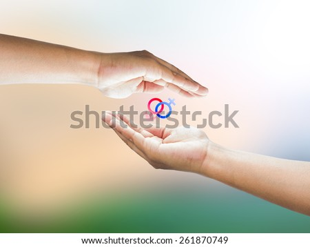 Human hand holding Mars Venus or Male Female symbol. Safe Sex concept. - stock photo