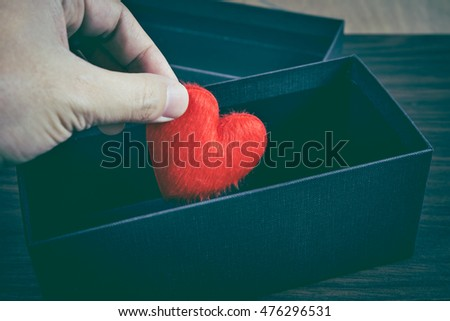 Human hand holding or putting a red heart-shaped in a black gift box for a Valentine's day, concept of care and love, colorized vintage picture style, gift box is placed on a wooden table